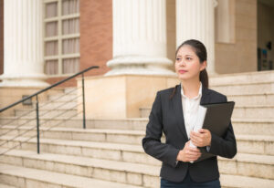 Business woman standing in front of court and holding legal documents waiting for customers ready to handle case.