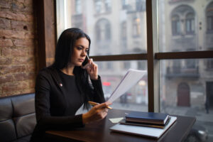 Female proud candidate reading summary during cellphone conversation