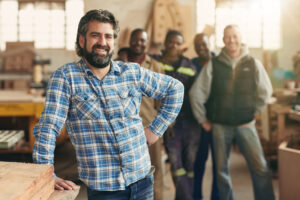 A smiling carpenter with his team - dasg